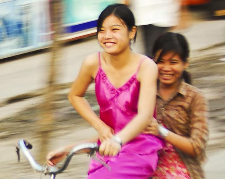 Girls share a bike on a Saigon street