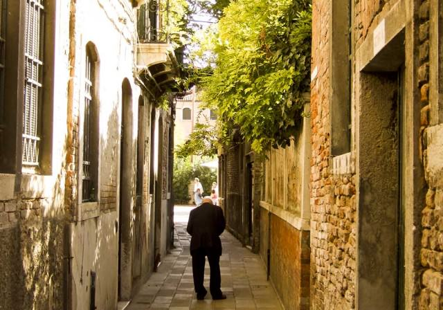 An old man on a narrow lane in Venice
