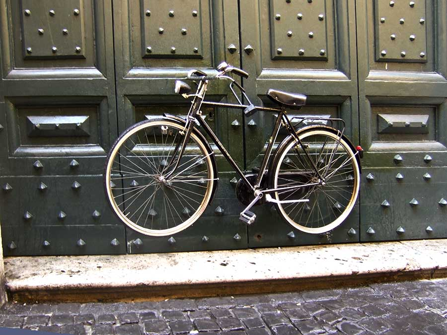A bicylcle seems to float in space chained to a door in Rome