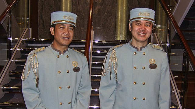 Crew in page boy uniforms on Crystal Serenity
