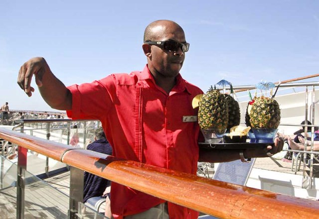 waiter delivers pineapple drinks on Carnival Liberty