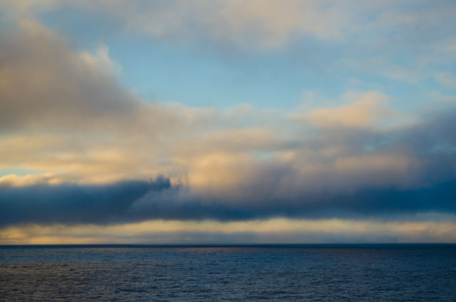 """This evening, enough broken cloud existed to offer our first """"true"""" sunset at sea. Photo © 2012 Aaron Saunders"""