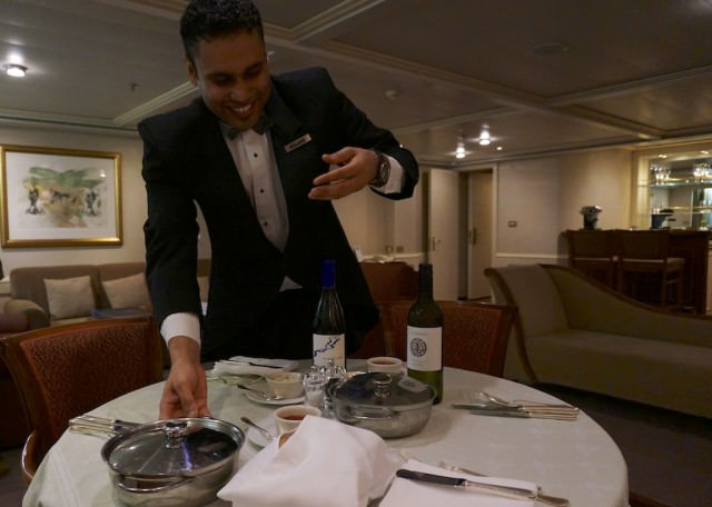 Roland, my butler, serves dinner in my suite. © 2014 Ralph Grizzle