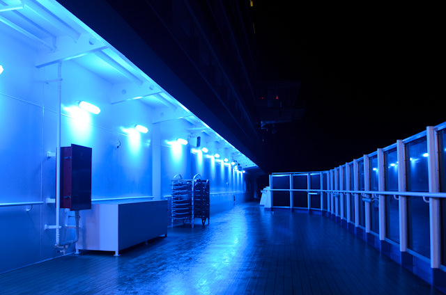 Blue navigation-friendly lighting illuminates the first quarter of the Promenade Deck on Deck 5 aboard Carnival Breeze as we sail into the night. Photo © 2014 Aaron Saunders