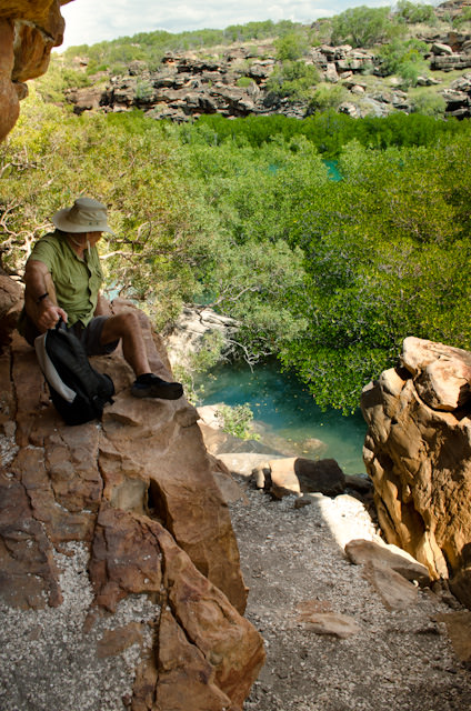 Many of these ancient cave drawings were painted in remote locations that were difficult to access. Here, one of the guests aboard Silver Discoverer looks down at the water below, and the path we hiked up on. Photo © 2014 Aaron Saunders