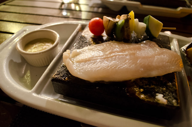 My Basa Fish grilling atop a volcanic 'hot rock', poolside. Photo © 2014 Aaron Saunders