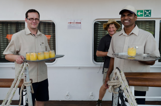 Zak and Preston offer welcome aboard drinks, while Expedition Team member Malcolm hides in the background. Photo © 2014 Aaron Saunders