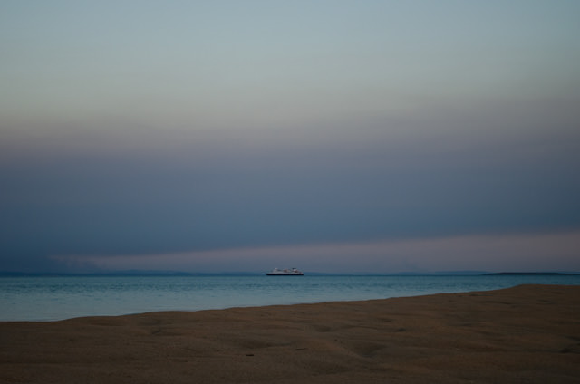 Silversea's Silver Discoverer off in the distance, as seen from the sand bar. Photo © 2014 Aaron Saunders