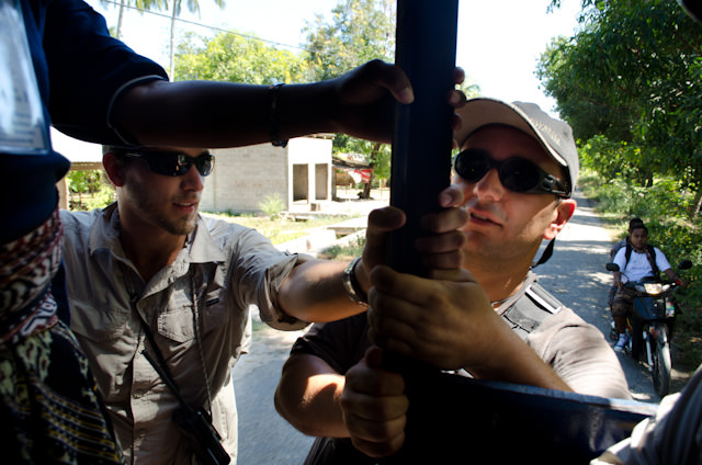 Silver Discoverer Expedition Team members Tim (left) and Juan (right) hang on to the back of our truck as we make our way to our local village experience in Savu, Indonesia. Photo © 2014 Aaron Saunders