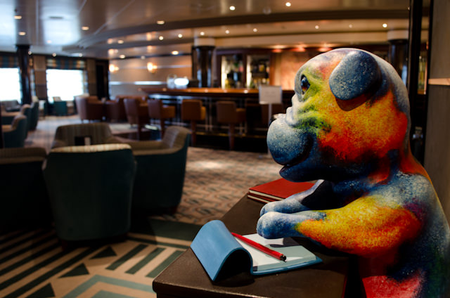 """There's plenty of eclectic and interesting artwork throughout the ship - like this piece titled """"Back to School Blues."""" Perhaps more interesting: if you see a piece of art you like, you can actually purchase it. Mr. Blue here goes for $9,500. Photo © 2014 Aaron Saunders"""
