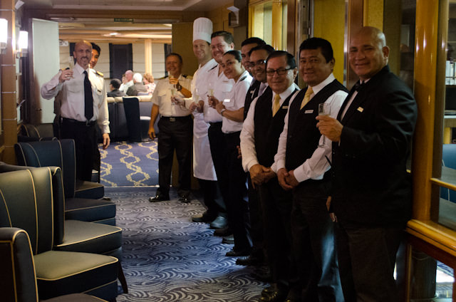 Members of the fabulous crew of the Silver Galapagos line the hallway on Deck 3 leading into the Explorer's Lounge for the Farewell Toast. Photo © 2014 Aaron Saunders