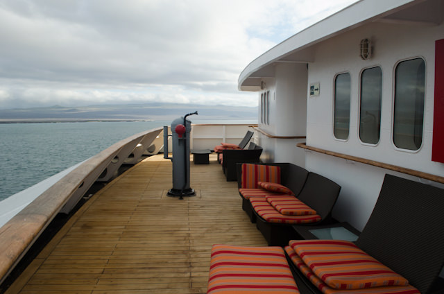 ...a forward-facing deck space on Deck 5. This is technically part of the shared balcony for Terrace Suite guests, so perhaps don't make yourself cozy in one of the loungers. At anchor, it's quite pleasant here. Underway - as seen here - the wind has a tendency to blow the cushions off the chairs. Photo © 2014 Aaron Saunders