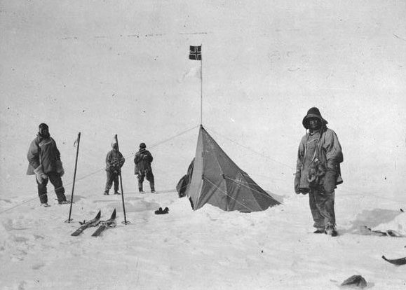 "Robert Falcon Scott stands before the tent that Roald Amundsen erected at the South Pole. Amundsen beat Scott there by five weeks. Scott is standing on the far left, with Edgar ""Taff"" Evans on the far right in the foreground. Photo courtesy of Wikipedia / Creative Commons."