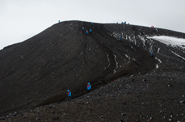 Guests from the FRAM hike up the volcanic hills of Telefon Bay, nearly invisible save for their blue jackets. Photo © 2015 Aaron Saunders