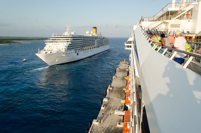 Costa Luminosa departs Costa Maya as guests from Carnival Freedom look on. Photo © 2015 Aaron Saunders