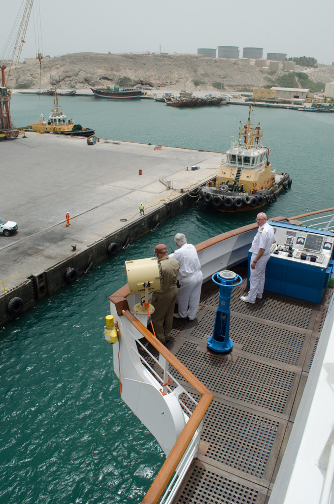 Maneuvering into port: Captain, Staff Captain and Omani Pilot stand on the portside bridge wing of the Silver Wind. Photo © 2015 Aaron Saunders