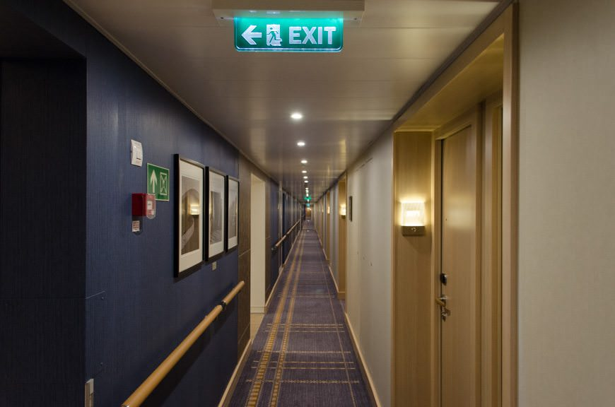 Stateroom corridors feature attractive blue paneling on the inner bulkhead walls. Photo © 2015 Aaron Saunders