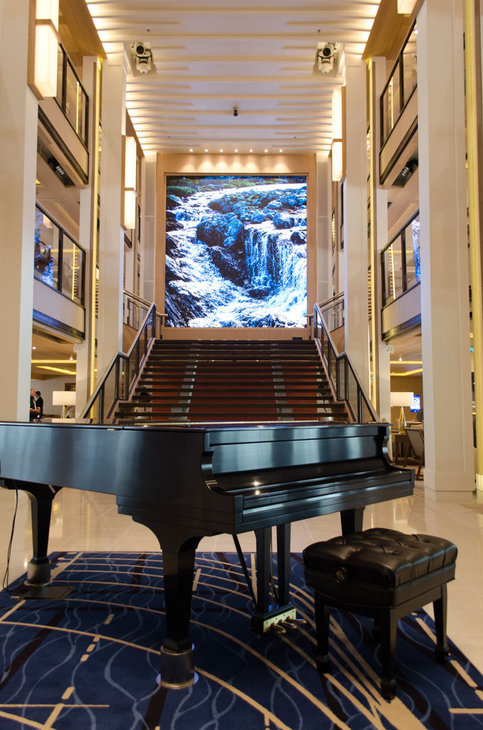 """Welcome Aboard! The first space most guests will see is the spectacular Atrium that spans Decks 1, 2 and 3. The """"painting"""" at the top of the stairs is actually a high-resolution digital screen. Photo © 2015 Aaron Saunders"""
