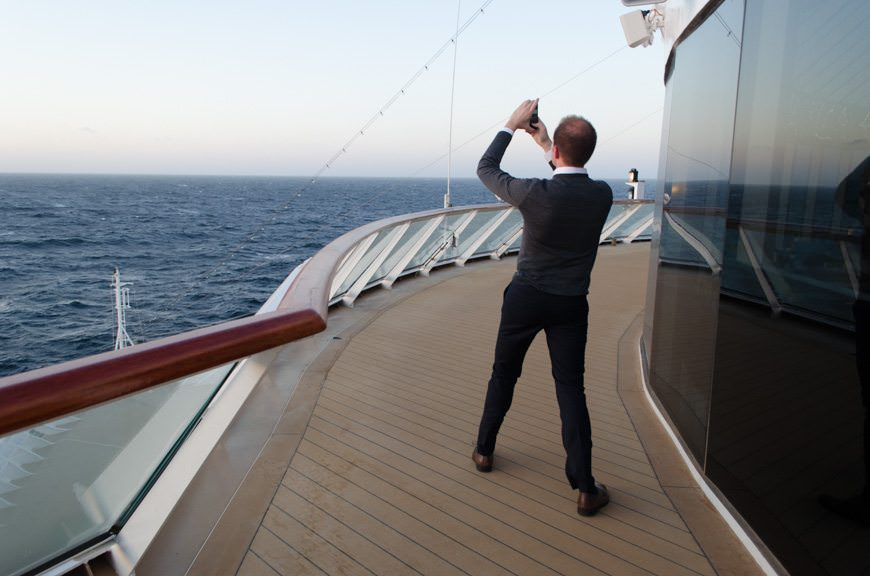 A guest braces themselves against the wind forward of the Explorer's Lounge as Viking Star makes her way closer to Bergen, Norway. Photo © 2015 Aaron Saunders