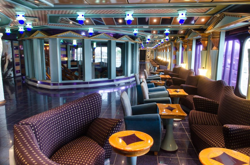 The long promenade along the starboard side of Deck 3 provides additional seating, but hides the cozy Sam's Piano Bar that's located through the entrance off to the left side of the photo. Photo © 2015 Aaron Saunders