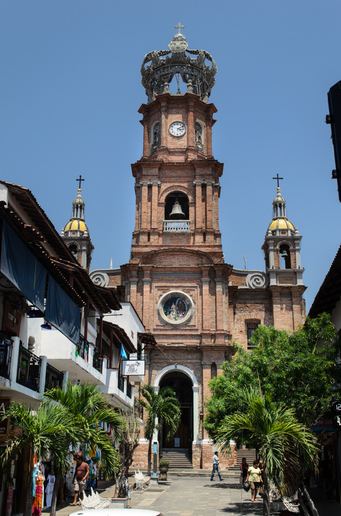 Puerto Vallarta's Church of Our Lady of Guadalupe. The steel crown at the top of the clock tower was once blown off by a hurricane, and had to be re-mounted. Photo © 2015 Aaron Saunders