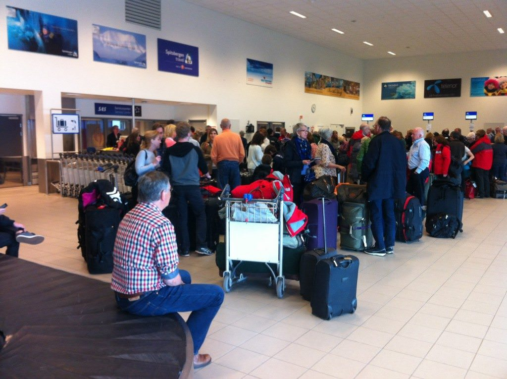 Oslo Bound: guests queue up at Longyearbyen Airport on Tuesday, July 14 for our charter flight to Oslo - which did depart! Photo © 2015 Aaron Saunders