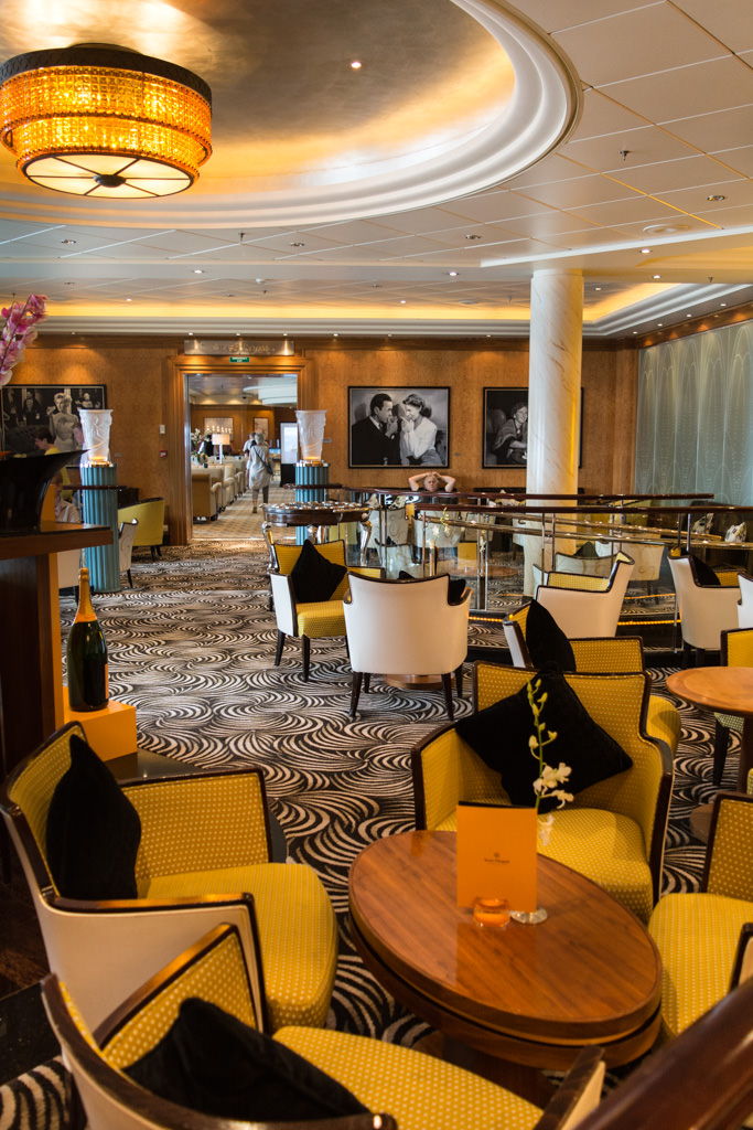 There's so much to do aboard Queen Mary 2 that finding a spot to sit is rarely an issue. Shown here is the striking Veuve Cliquot Champagne Bar, with the ever-popular Chart Room beyond it.  Photo © 2015 Aaron Saunders