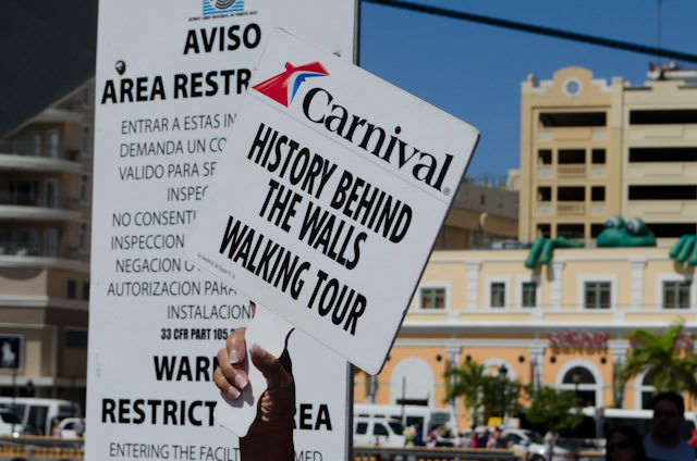 A guide holds up a sign for Carnival guests who have booked excursions through the ship in San Juan, Puerto Rico. Excursions booked through your ship are protected from delays; independent tours are not. Photo © 2014 Aaron Saunders