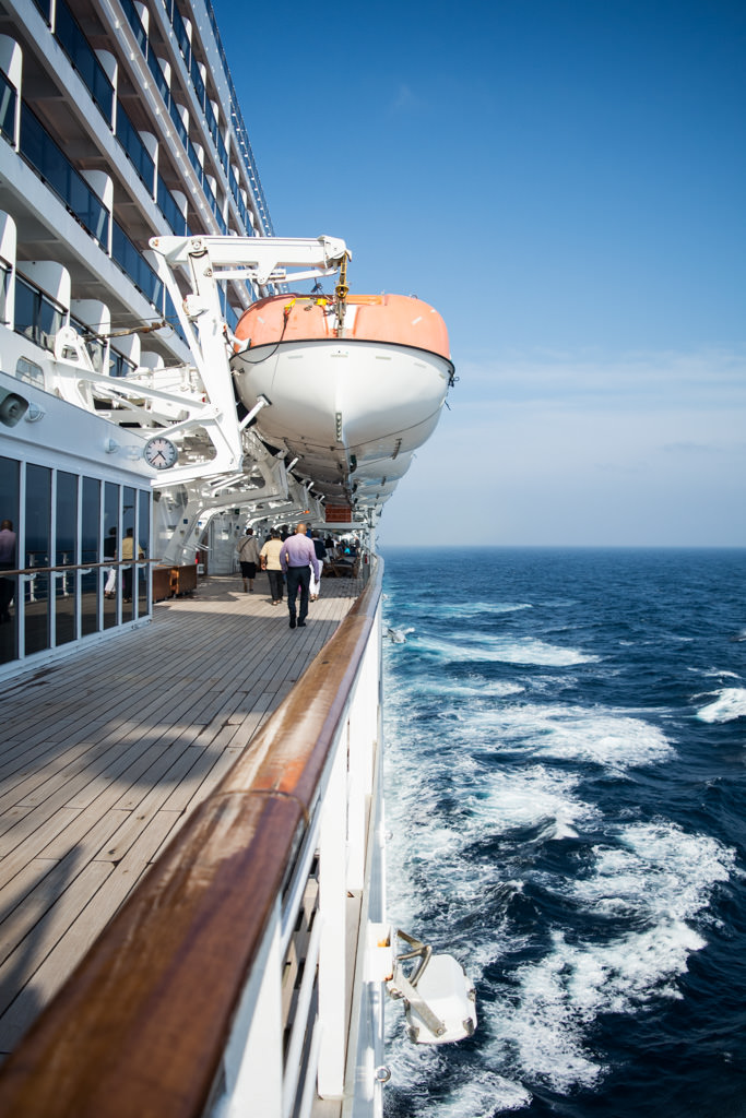 Some hearty souls brave the wind once the sun returned. Queen Mary 2's boat deck is twice as high off the ocean as most modern cruise ships, protecting the lifeboats from potentially-damaging waves. Photo © 2015 Aaron Saunders