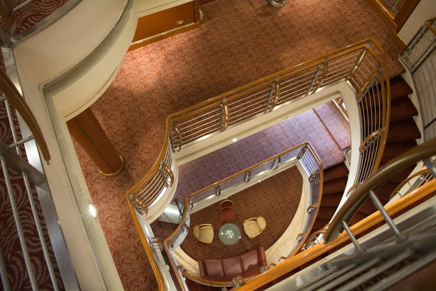 While Silver Whisper may lack a soaring atrium, she does feature an attractive open-air staircase design. Photo © 2015 Aaron Saunders