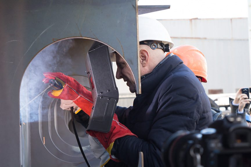 Silversea CEO Enzo Visone performs the first weld of the coins into the keel of the Silver Muse. Photo © 2015 Aaron Saunders