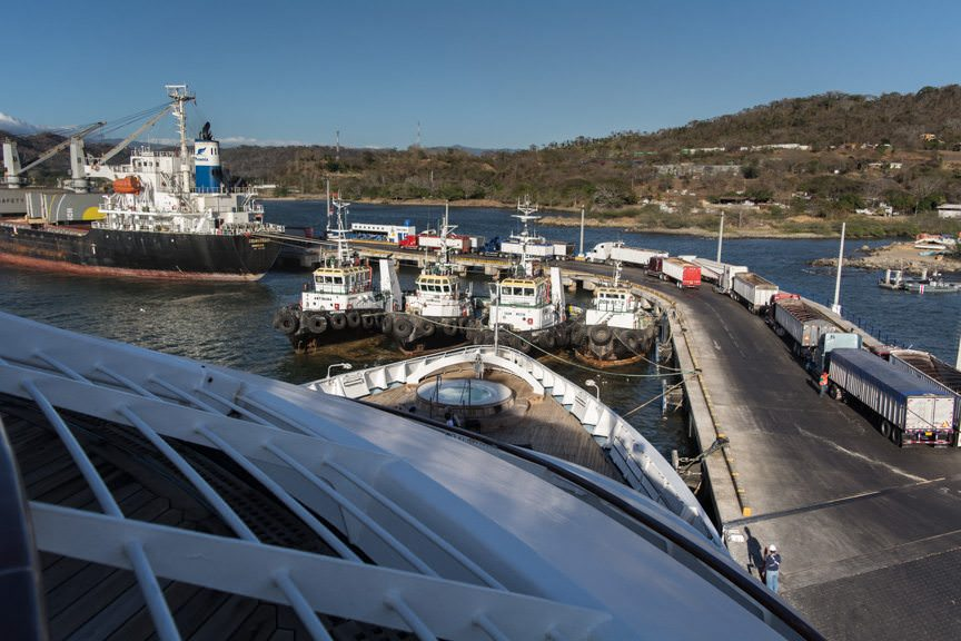 Overlooking the Bow: Star Breeze marks a decided contrast between her and the cargo ship awaiting shipments from a line of 18-wheelers. Photo © 2016 Aaron Saunders