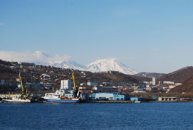 The two sleeping volcanoes of Koryaksky and Avachinsky brood over the waterfront of Petropavlovsk